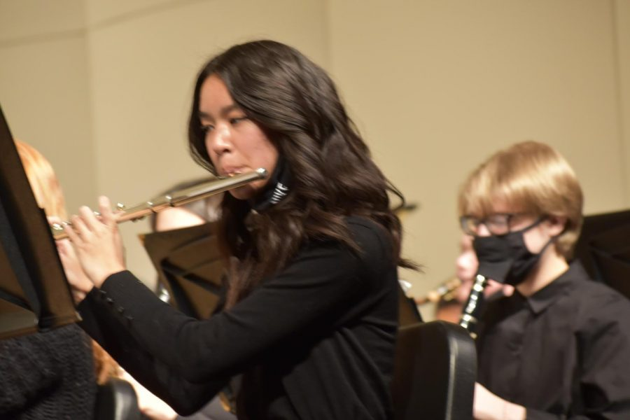 Kristen Tu 23 is reading her sheet music while performing at the band concert. She plays the flute for concert band.