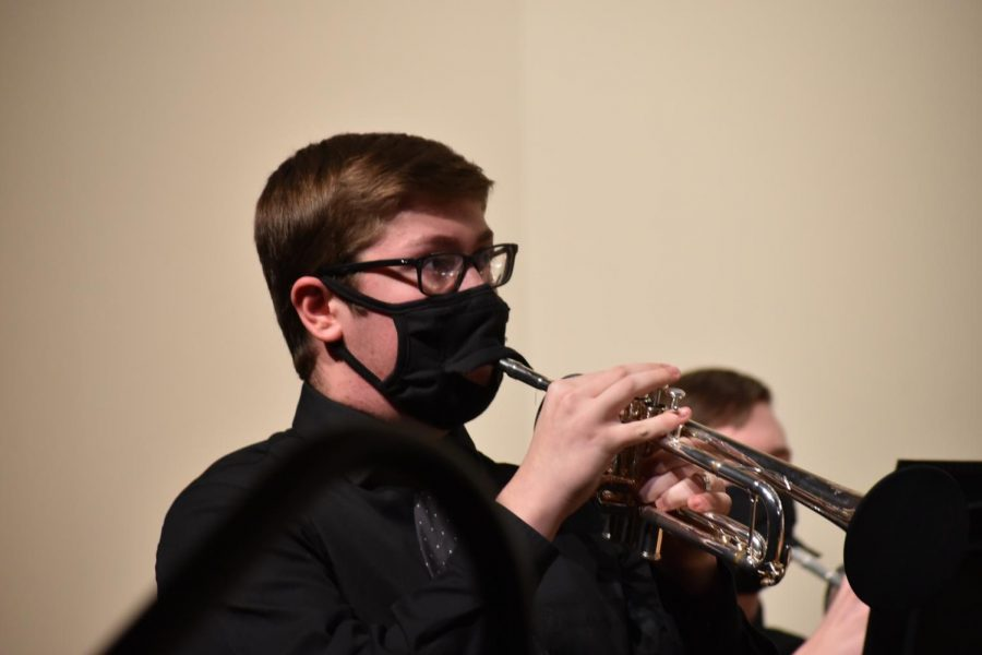 Elijah Caliger 23 is focused on the band director while performing. He plays trumpet for concert band.