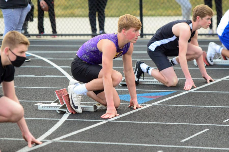 Owen Helgeson '23 starting down in his block for the 4x110 meter shuttle hurdle race.