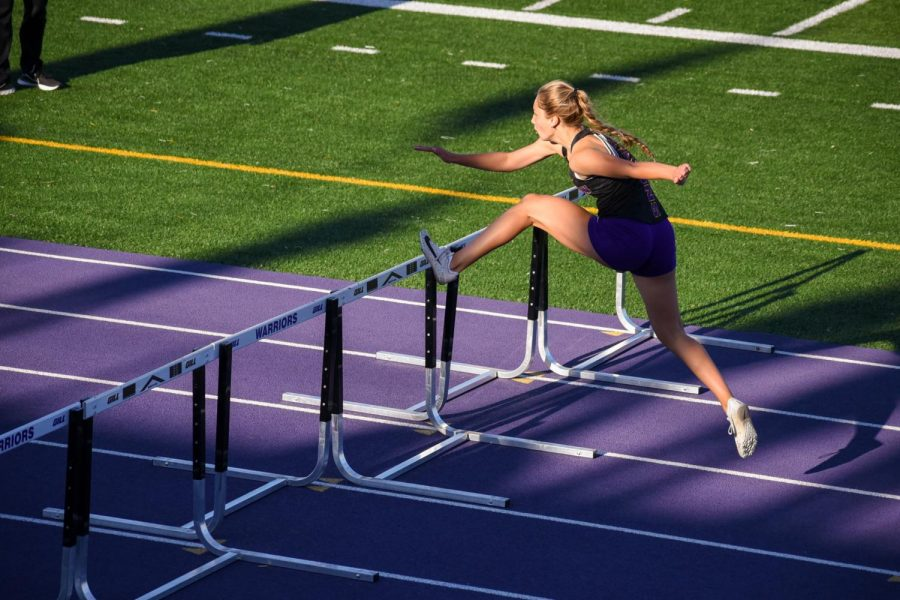 Ella Smithson '24 sprinting through the end of the girls 4x100 meter shuttle hurdle relay.