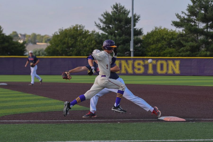 JT Garcia '22 sprints to first base while an Urbandale defender makes an error on June 23, 2021.