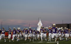 The varsity football team running out of the band tunnel to the sideline.  The Dragons in the final minute pulled out the win over Cedar Falls with a score of 28-22
